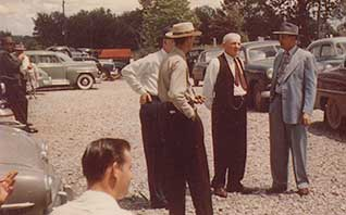 Great Grandfather 'Dad' (in the vest and red tie) holding conversational court in the church parking lot. To his left, the teacher at the one-room Big Ridge schoolhouse.