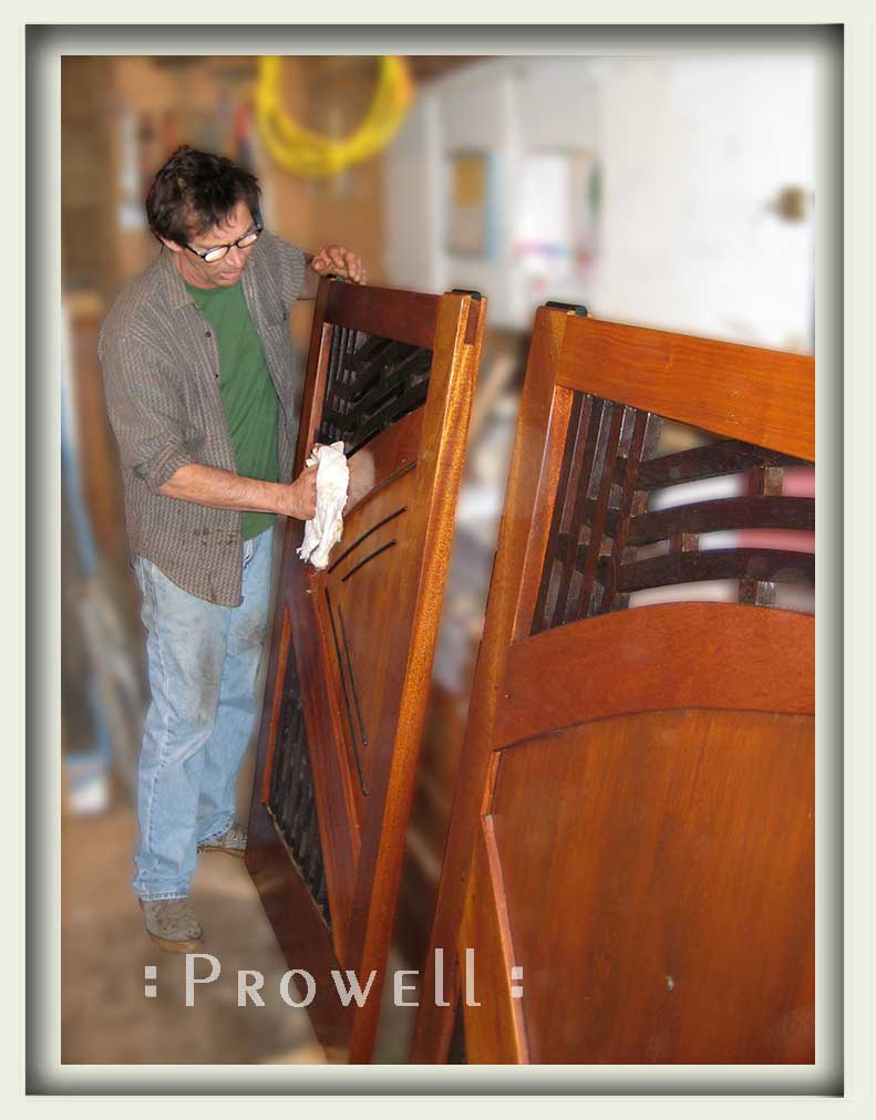 Photograph in the wood shop with charles applying the finish to modern wooden gate #202