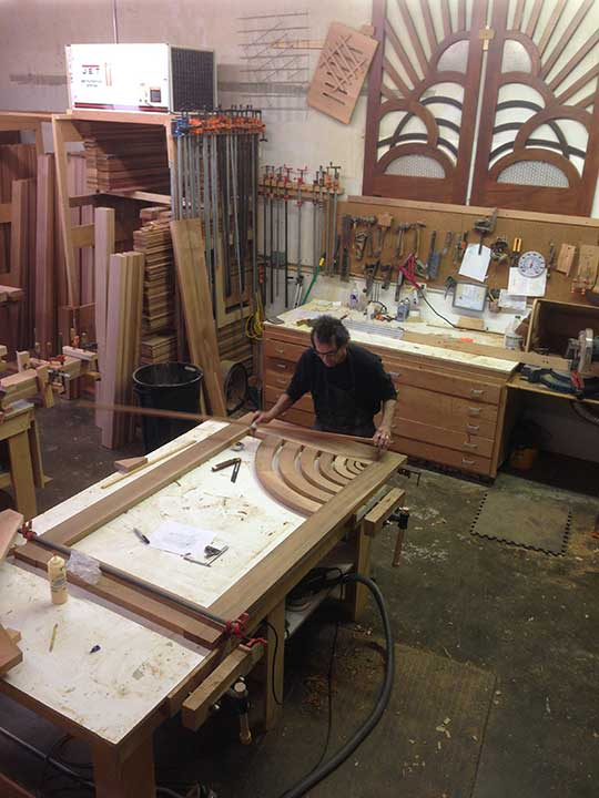 shop photograph showing charles prowell designing the modern wood gate #206