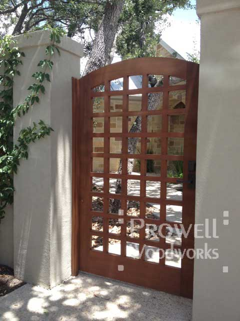 Site photograph showing the arching wood Gate 27 in Austin,Texas between stucco columns